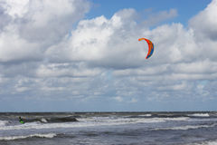 Kitesurfing dude passing by. Kitesurfer passing by in the surf Royalty Free Stock Photos