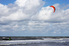 Kitesurfing dude passing by. Kitesurfer passing by in the surf Royalty Free Stock Image