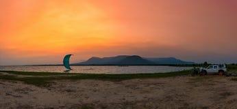 Kitesurfing en la puesta del sol con Mountain View Imagen de archivo