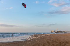 Kitesurfing in the evening along the Dutch coast of Scheveningen. Kite surfing in the evening along the Dutch coast with a view at the famous Pier of Stock Photo