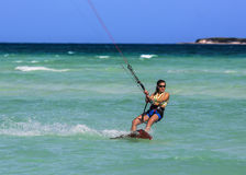 Kitesurfing girl. A young woman kitesurfer rides in greenish-blue sea under clear skyes Stock Images