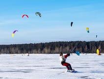 Kitesurfing i vintern Åka skridskor på isen i vinden Arkivbild