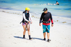 Kitesurfing instructor and female student preparing lines on beach Royalty Free Stock Photography