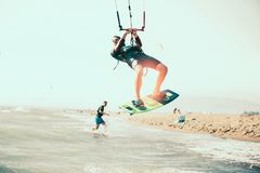 Kitesurfing Kiteboarding action photos. Man among waves quickly goes Stock Images