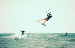 Kitesurfing Kiteboarding action photos. Man among waves quickly goes Royalty Free Stock Image