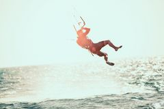 Kitesurfing Kiteboarding action photos. Man among waves quickly goes Stock Photography
