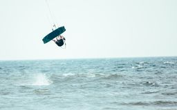 Kitesurfing Kiteboarding action photos man among waves. Quickly goes Stock Photography