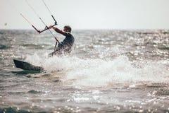 Kitesurfing Kiteboarding action photos man among waves. Quickly goes Stock Image