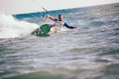 Kitesurfing Kiteboarding action photos man among waves. Quickly goes Stock Photos