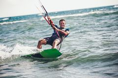 Kitesurfing Kiteboarding action photos man among waves. Quickly goes Stock Photo