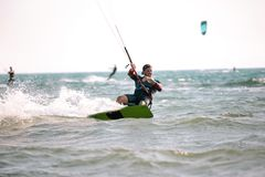 Kitesurfing Kiteboarding action photos man among waves. Quickly goes Royalty Free Stock Image