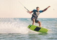 Kitesurfing, Kiteboarding action photos, man among waves. Quickly goes Stock Photos