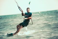 Kitesurfing Kiteboarding action photos. Man among waves quickly goes Royalty Free Stock Photos