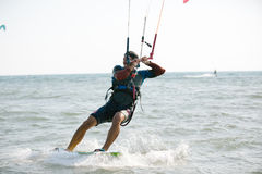 Kitesurfing, Kiteboarding action photos. Man among waves quickly goes Royalty Free Stock Photo