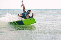 Kitesurfing, Kiteboarding action photos. Man among waves quickly goes Royalty Free Stock Photos