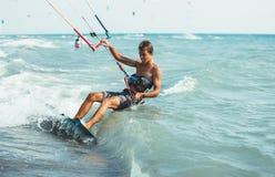 Kitesurfing,. Kiteboarding action photos, man among waves quickly goes Royalty Free Stock Image