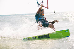 Kitesurfing. Kiteboarding action photos, man among waves quickly goes Stock Photography