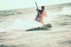 Kitesurfing Kiteboarding action photos. Man among waves quickly goes Stock Photo
