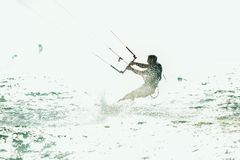 Kitesurfing Kiteboarding action photos man among waves. Quickly goes Stock Images