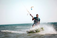 Kitesurfing Kiteboarding action photos man among waves. Quickly goes Royalty Free Stock Photography