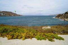 Kitesurfing, los deportes acuáticos extremos en fuerte viento en la bahía de Korfos vara en fondo azul del mar y del cielo con la Imagen de archivo libre de regalías