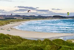 Kitesurfing men in action on stormy sunset evening at Brusand Beach, Norway. Royalty Free Stock Images