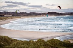 Kitesurfing men in action on stormy sunset evening at Brusand Beach, Norway. Royalty Free Stock Photos