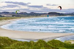 Kitesurfing men in action on stormy sunset evening at Brusand Beach, Norway. Royalty Free Stock Image