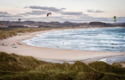 Kitesurfing men in action on stormy sunset evening at Brusand Beach, Norway. Royalty Free Stock Photography