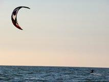 Kitesurfing no por do sol Imagens de Stock Royalty Free