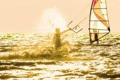 Kitesurfing och surfing på solnedgången i panelljuset Arkivbild