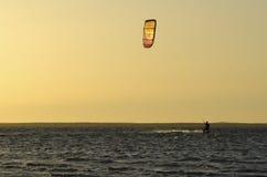 Kitesurfing på solnedgången Arkivfoto