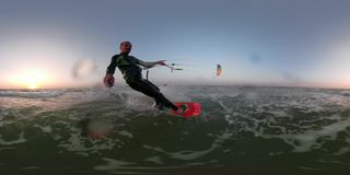 A happy man in a diving suit is engaged in kitesurfing at dawn, a selfie stick with a camera 360. Kitesurfing on the sea, holds a selfie stick and controls a stock video footage