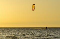 Kitesurfing at sunset Stock Images