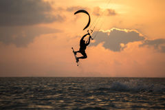 Kitesurfing. Various tricks done by rider on a kiteboard shot at sunset with beautiful backlit Royalty Free Stock Image