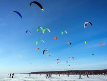 Kitesurfing in the winter on snowboard or ski. Skating on the ice in the wind. Beautiful colored sails stock photo