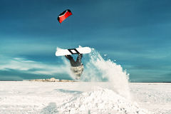 Kiting on a snowboard on a frozen lake. Kite in the blue sky, winter riding a kite, sport on a frozen lake Royalty Free Stock Image