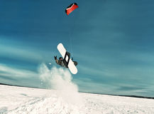 Kiting on a snowboard on a frozen lake. Kite in the blue sky, winter riding a kite, sport on a frozen lake Royalty Free Stock Photo