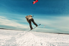 Kiting on a snowboard on a frozen lake. Kite in the blue sky, winter riding a kite, sport on a frozen lake Stock Image
