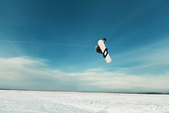 Kiting on a snowboard on a frozen lake. Kite in the blue sky, winter riding a kite, sport on a frozen lake Royalty Free Stock Photos