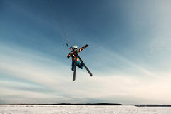 Kiting on a snowboard on a frozen lake. Kite in the blue sky, winter riding a kite, sport on a frozen lake Stock Photography