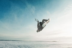 Kiting on a snowboard on a frozen lake. Kite in the blue sky, winter riding a kite, sport on a frozen lake Stock Photos