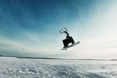 Kiting on a snowboard on a frozen lake. Kite in the blue sky, winter riding a kite, sport on a frozen lake Stock Images