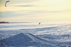 Kiting on a snowboard on a frozen lake. Wintery kiting on a snowboard on a frozen lake Stock Photos