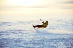 Kiting on a snowboard on a frozen lake. Wintery kiting on a snowboard on a frozen lake Royalty Free Stock Images