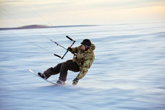 Kiting on a snowboard on a frozen lake. Wintery kiting on a snowboard on a frozen lake Royalty Free Stock Image