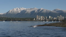 Kitsilano Beach, Mountain Snow, English Bay 4K. Kitsilano Beach on English Bay in the early morning. In the background are the snowcapped North Shore Mountains stock video