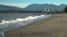 Kitsilano Beach Waves, Vancouver 4K UHD. Kitsilano Beach on English Bay in the morning. In the background are the North Shore Mountains. Vancouver, British stock video footage