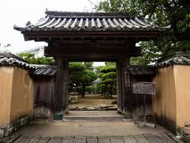 Traditional Japanese gate in Kitsuki city, Oita prefecture, Japan. Kitsuki, Japan - October 31, 2016: Entrance to a local elementary school guarded by 200 year royalty free stock photos