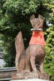Kitsune, the fox, holds a message in its mouth at Fushimi Inari. Kyoto, Japan - September 17, 2016: Fushimi Inari Taisha Shinto Shrine. Kitsune, the brown fox Royalty Free Stock Photos